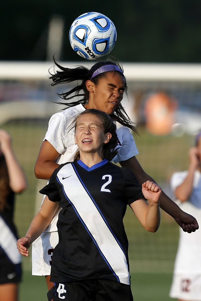Photo - Deer Creek's Ashton England, front, and Carl Albert's Lexi Blackwell leap for the ball during the Class 5A girls state soccer championship between Deer Creek and Carl Albert in Norman, Okla., Saturday, May 17, 2014. Photo by Bryan Terry, The Oklahoman
