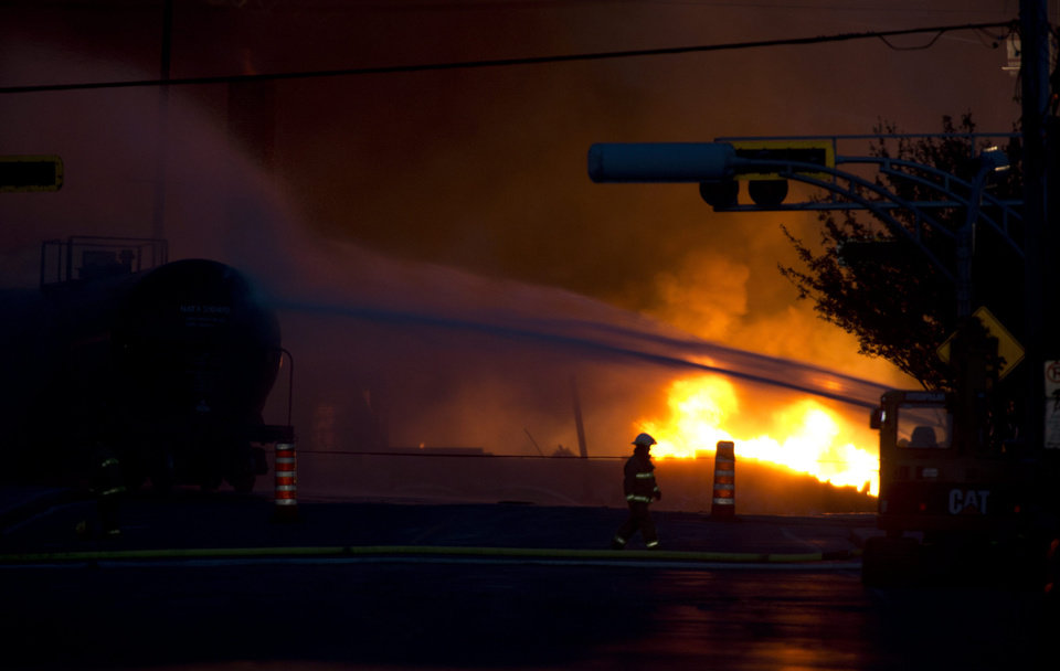 Photo - A fire keeps burns after railway cars that were carrying crude oil derailed in downtown Lac Megantic, Quebec, Saturday, July 6, 2013. (AP Photo/The Canadian Press, Paul Chiasson)