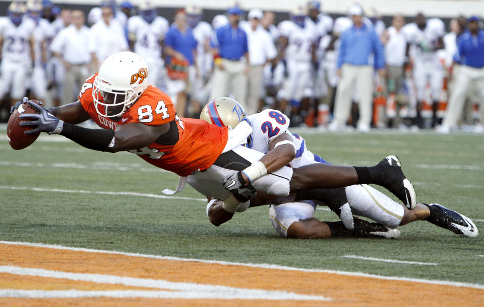Photo - Oklahoma State wide receiver Hubert Anyiam (84) stretches for a touchdown as Tulsa's Lowell Rose (28) tackles him during the college football game between the University of Tulsa (TU) and Oklahoma State University (OSU) at Boone Pickens Stadium in Stillwater, Oklahoma, Saturday, September 18, 2010. Photo by Sarah Phipps, The Oklahoman