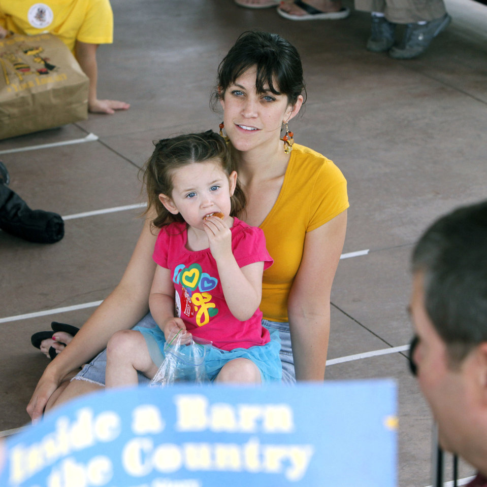 Photo - Left: Kaitlyn Davies, 2, and her mother, April, listen as OETA's Dick Pryor reads a book during the Read Across Oklahoma event. Photo by Paul Hellstern,  The Oklahoman