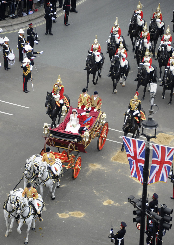 Photo - Britain's Prince William and Kate, the Duchess of Cambridge, travel in the 1902 State Landau carriage along the processional route to Buckingham Palace, London, Friday April 29, 2011. (AP Photo/Damien Meyer, Pool)  ORG XMIT: RWDJ122