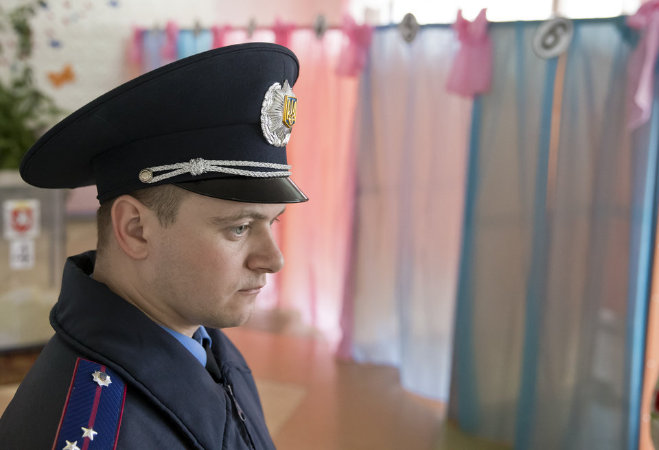 Photo - A Ukrainian policeman supervises activity in a voting station in Perevalne, Ukraine, Sunday, March 16, 2014. Residents of Ukraine's Crimea region are voting in a contentious referendum on whether to split off and seek annexation by Russia. (AP Photo/Vadim Ghirda)