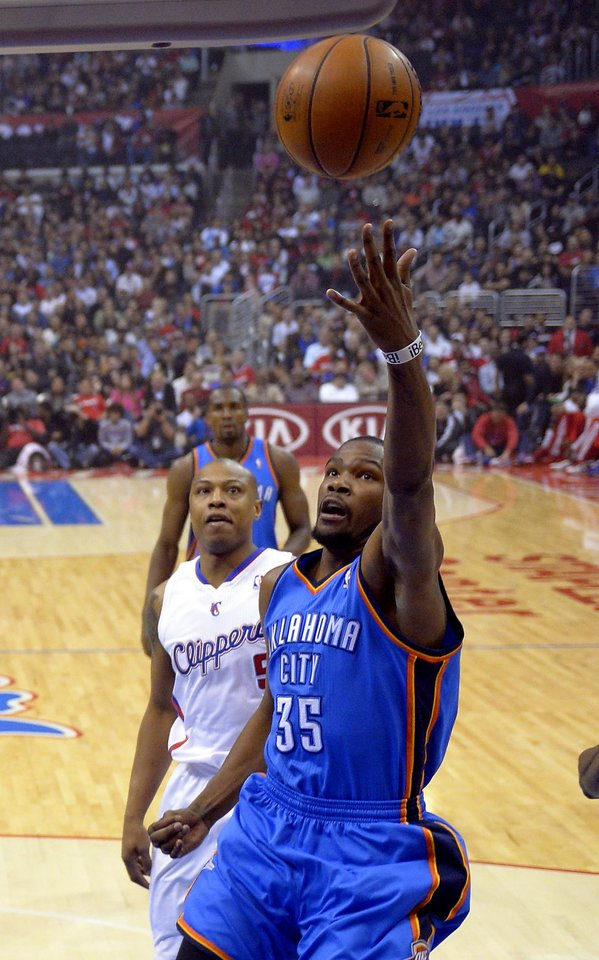 Photo - Oklahoma City Thunder forward Kevin Durant, right, puts up a shot as Los Angeles Clippers forward Caron Butler defends during the first half of their NBA basketball game, Tuesday, Jan. 22, 2013, in Los Angeles.  (AP Photo/Mark J. Terrill) ORG XMIT: LAS101