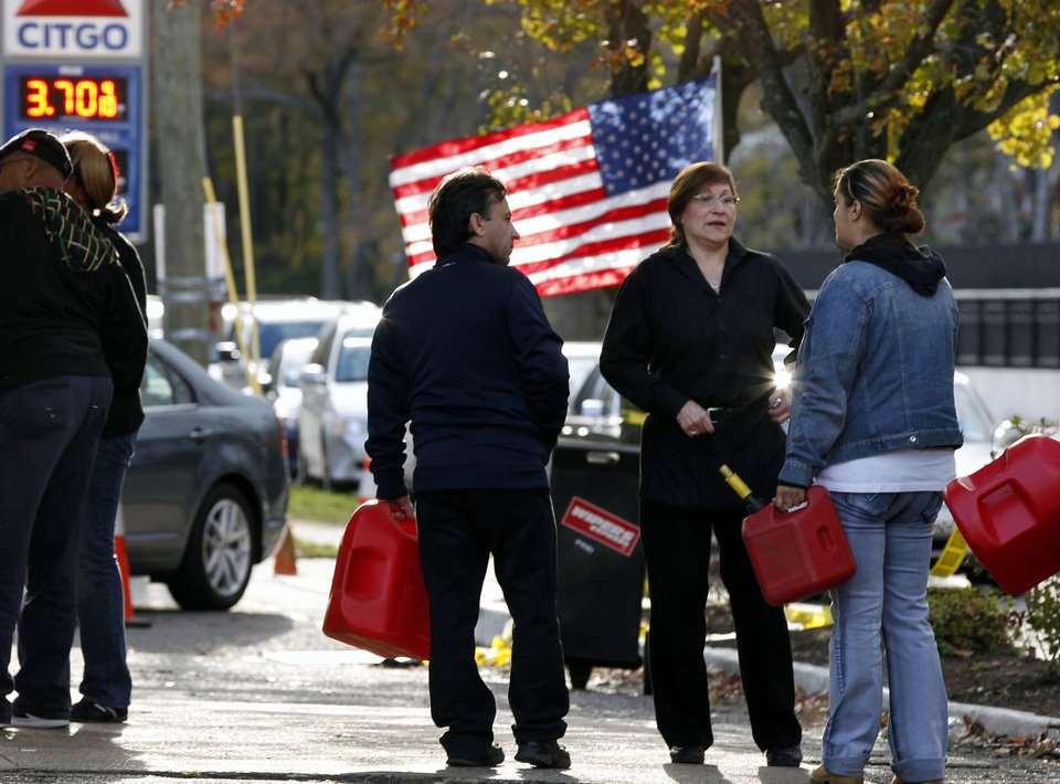 FILE - In this Saturday, Nov. 3, 2012, file photo, people wait in line with containers to purchase gasoline at filling station in Metuchen, N.J. The price of oil is slightly higher Monday, Nov. 5, 2012, as investors remain cautious ahead of the U.S. presidential election. They\'re also assessing how much demand for oil has dropped in the storm-stricken Northeast. (AP Photo/Mel Evans, File)