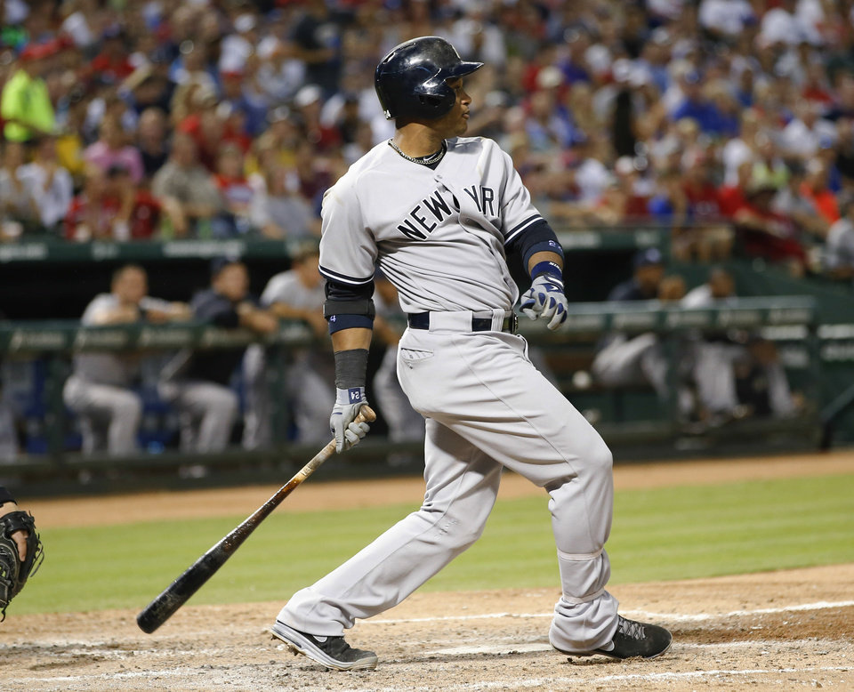 Photo - New York Yankees' Robinson Cano follows through on an RBI single against the Texas Rangers during the sixth inning of a baseball game, Wednesday, July 24, 2013, in Arlington, Texas. (AP Photo/Jim Cowsert)
