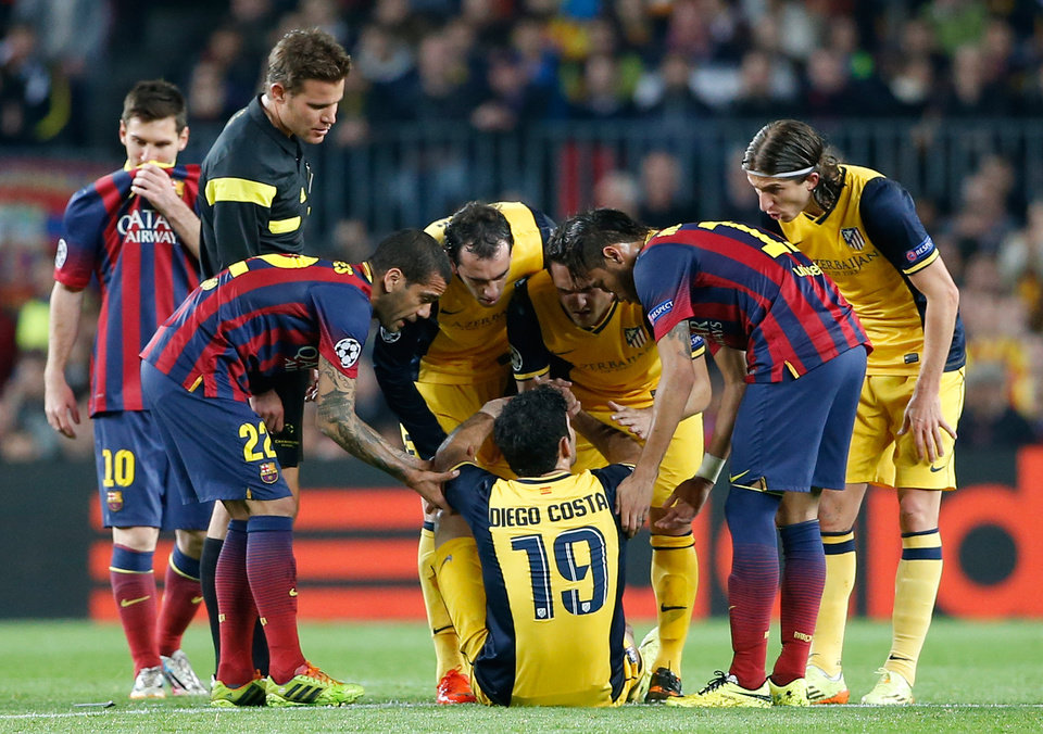 Photo - Players check on Atletico's Diego Costa, center, after he injured himself during a first leg quarterfinal Champions League soccer match between Barcelona and Atletico Madrid at the Camp Nou stadium in Barcelona, Spain, Tuesday April 1, 2014. (AP Photo/Emilio Morenatti)