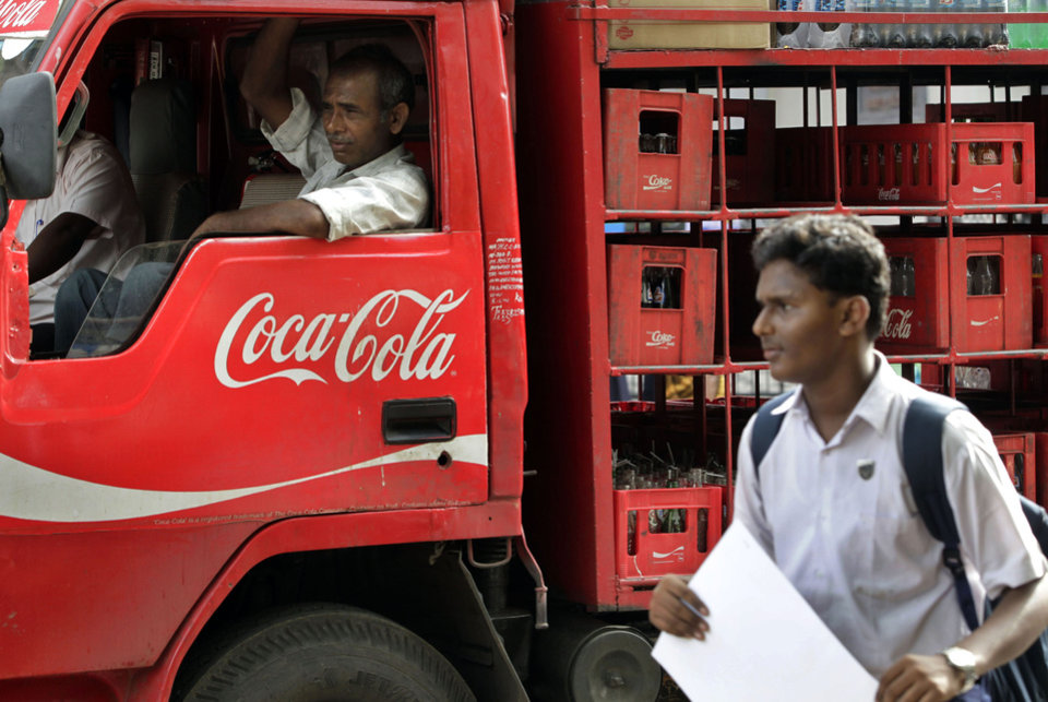 Photo - FILE - In this June 26, 2012 file photo, a man walks past a truck that distributes Coca Cola in Mumbai, India. An increasing thirst for Coca-Cola products in China, India and the Middle East helped boost the company's international sales by 3 percent in the second quarter while volume remained flat in North America. (AP Photo/Rajanish Kakade, File)