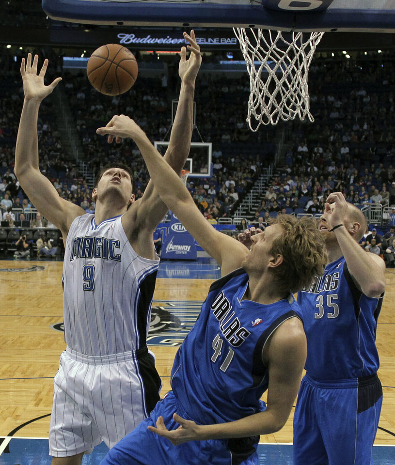 Orlando Magic's Nikola Vucevic (9), of Montenegro, goes after a rebound against Dallas Mavericks' Dirk Nowitzki (41), of Germany, and Chris Kaman (35),  during the first half of an NBA basketball game, Sunday, Jan. 20, 2013, in Orlando, Fla. (AP Photo/John Raoux)