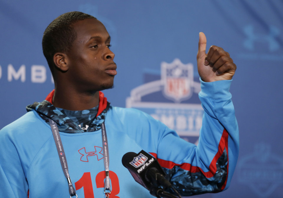 West Virginia quarterback Geno Smith begins a news conference at the NFL football scouting combine in Indianapolis, Friday, Feb. 22, 2013. (AP Photo/Michael Conroy)