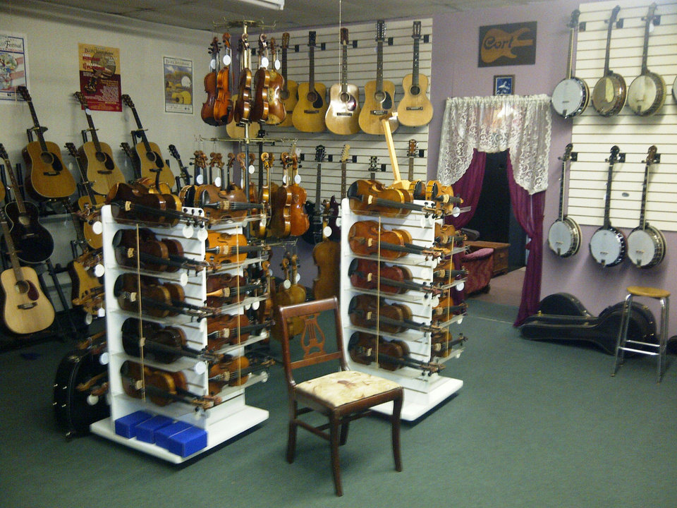 Photo - Fiddles and guitars are on display at Byron Berline's Double Stop Fiddle Shop in Guthrie. PHOTO PROVIDED.