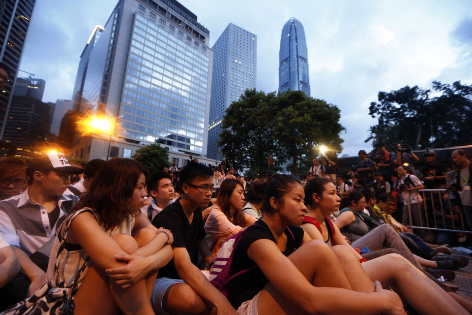 Photo - Hundreds of protesters stage a peaceful sit-ins overnight on a street in the financial district in Hong Kong Wednesday, July 2, 2014, following a huge rally to show their support for democratic reform and oppose Beijing's desire to have the final say on candidates for the chief executive's job. (AP Photo/Kin Cheung)