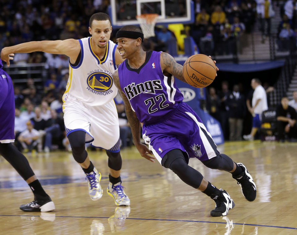 Photo - Sacramento Kings' Isaiah Thomas (22) dribbles past Golden State Warriors' Stephen Curry (30) during the first half of an NBA preseason basketball game Monday, Oct. 7, 2013, in Oakland, Calif. (AP Photo/Marcio Jose Sanchez)