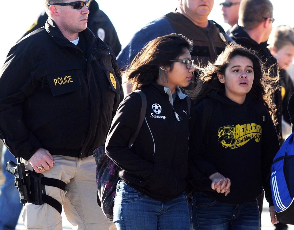 Photo - Students surrounded by officials are escorted from Berrendo Middle School after a shooting, Tuesday, Jan. 14, 2014, in Roswell, N.M. Roswell police said the suspected shooter was arrested at the school. The school had been placed on lockdown. No other details were yet available. (AP Photo/Roswell Daily Record, Mark Wilson)