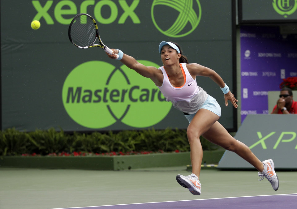 Photo - Caroline Garcia, of France, reaches as she tries to return to Serena Williams, of the United States, at the Sony Open tennis tournament in Key Biscayne, Fla., Saturday, March 22, 2014. (AP Photo/Alan Diaz)