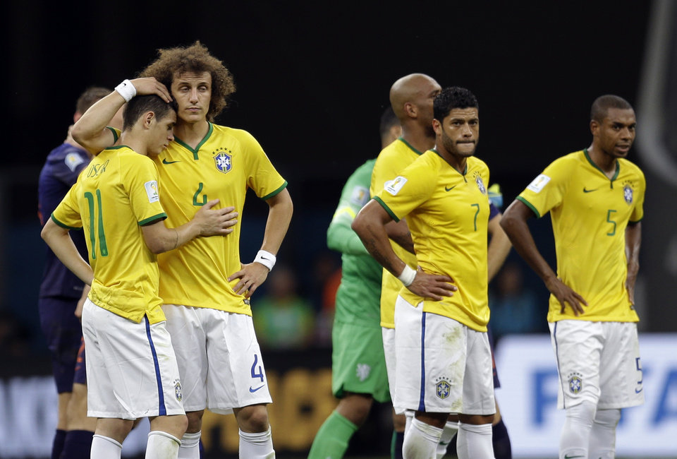 Photo - Brazil's David Luiz, left, and Oscar console each other alongside Hulk, center, and Fernandinho, right, after the Netherlands 3-0 victory over Brazil in the World Cup third-place soccer match between Brazil and the Netherlands at the Estadio Nacional in Brasilia, Brazil, Saturday, July 12, 2014. (AP Photo/Natacha Pisarenko)