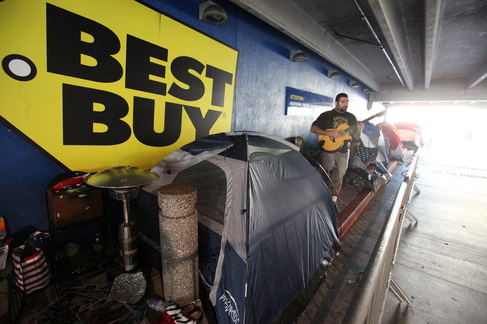 Photo -   Aaron Rodrigues waits in a line at Best Buy in the Van Nuys section of Los Angeles on Thur. Nov.22,2012. While stores typically open in the wee hours of the morning on the day after Thanksgiving known as Black Friday, openings have crept earlier and earlier over the past few years. Now, stores from Wal-Mart to Toys R Us are opening their doors on Thanksgiving evening, hoping Americans will be willing to shop soon after they finish their pumpkin pie. (AP Photo/Richard Vogel)