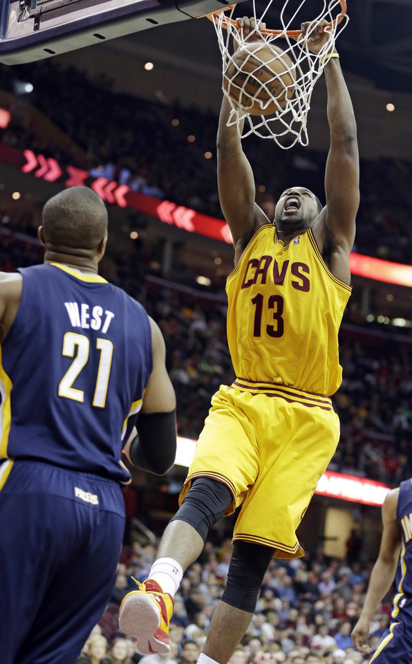 Photo - Cleveland Cavaliers' Tristan Thompson (13) dunks the ball in front of Indiana Pacers' David West (21) during the second quarter of an NBA basketball game Sunday, Jan. 5, 2014, in Cleveland. (AP Photo/Tony Dejak)