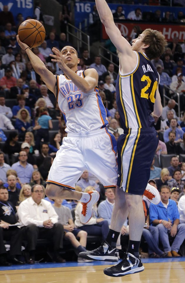 Photo - Oklahoma City Thunder's Kevin Martin (23) shoots around Utah Jazz's Gordon Hayward (20) during the NBA basketball game between the Oklahoma City Thunder and the Utah Jazz at Chesapeake Energy Arena on Wednesday, March 13, 2013, in Oklahoma City, Okla. Photo by Chris Landsberger, The Oklahoman
