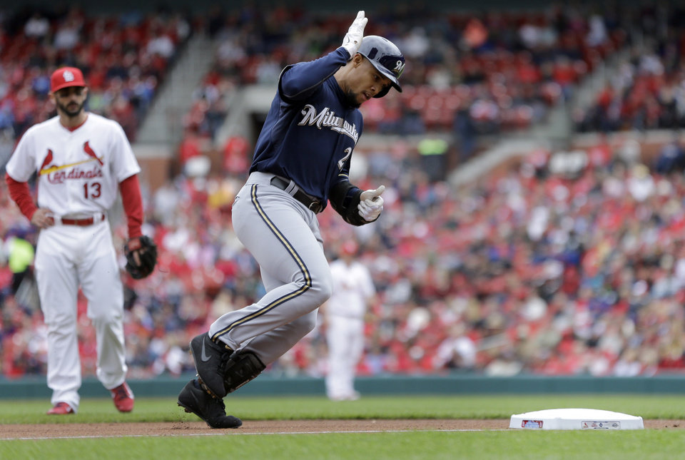Photo - St. Louis Cardinals third baseman Matt Carpenter, left, watches as Milwaukee Brewers' Carlos Gomez taps his helmet while rounding the bases after hitting a solo home run during the third inning of a baseball game against the St. Louis Cardinals Wednesday, April 30, 2014, in St. Louis. (AP Photo/Jeff Roberson)