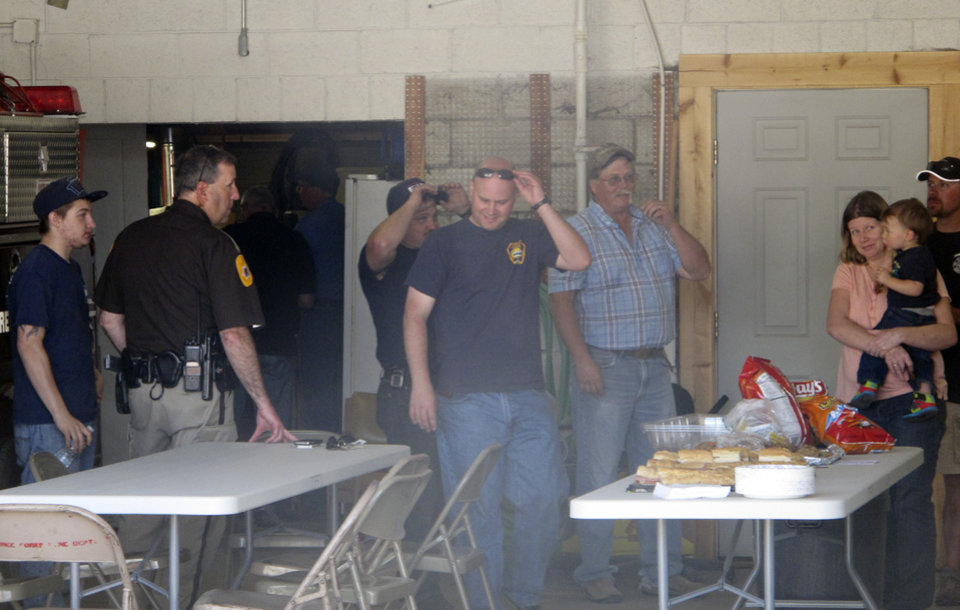 Photo - Firefighters, law-enforcement officers and residents gather inside the Three Forks, Montana, Fire Department on Friday, June 20, 2014, after learning Chief Todd Rummel died in a crash that also killed a family of five the night before. A memorial service is planned for June 25 for Rummel, who became chief in May. (AP Photo/Matt Volz)