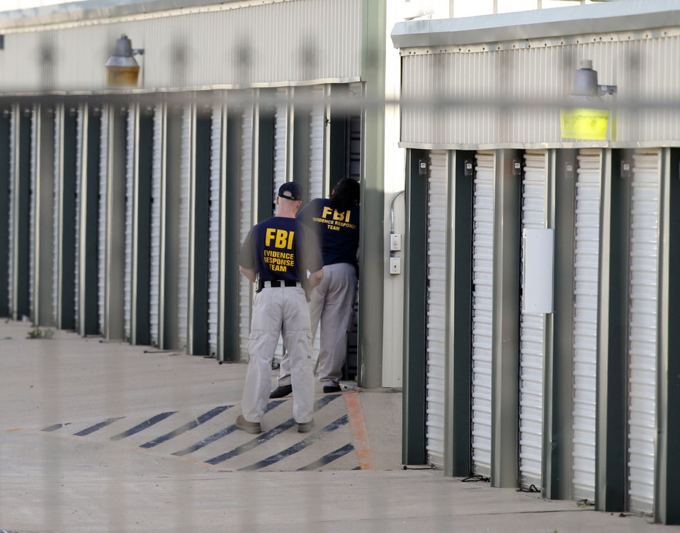 Photo - Authorities search a storage unit at Gibson Self Storage as they continue to investigate the slayings of Kaufman County District Attorney Mike McLelland, his wife and a top prosecutor, Saturday, April 13, 2013 in Seagoville, Texas. Authorities investigating the death of a Texas district attorney arrested Eric Williams, a former justice of the peace and charged him Saturday with making a