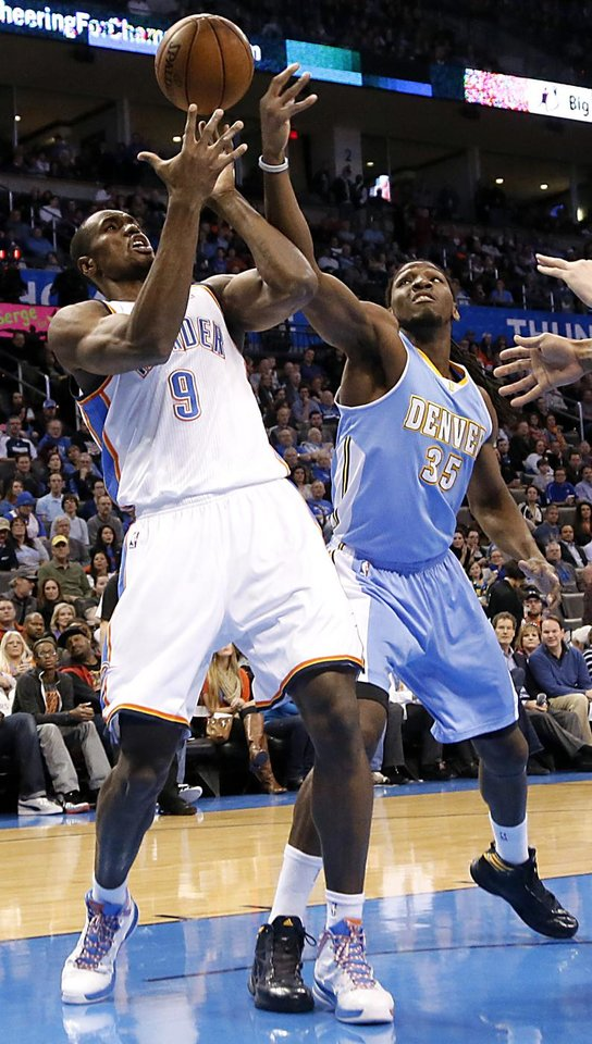 Photo - Oklahoma City's Serge Ibaka (9) fights for the ball with Denver's Kenneth Faried (35) during the NBA basketball game between the Oklahoma City Thunder and the Denver Nuggets at the Chesapeake Energy Arena on Wednesday, Jan. 16, 2013, in Oklahoma City, Okla.  Photo by Chris Landsberger, The Oklahoman