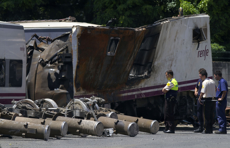 "Photo - Police and security officers look at a wrecked carriage in a train depot in Padron, near Santiago de Compostela, Spain, Friday July 26, 2013 after it was taken there from the scene of a train accident. Investigators have taken possession of the ""black boxes"" of the Spanish train that hurtled at high-speed along a curve and derailed, killing 80 people, a court official said Friday. Analysis will be performed to determine why the train was traveling far above the speed limit when it crashed near a station in Santiago de Compostela, in the northwestern Galicia region, said court spokeswoman Maria Pardo Rios. The train's operator remained hospitalised Friday and will be questioned by police but she said the interview will not happen Friday. (AP Photo/Lalo R. Villar)"