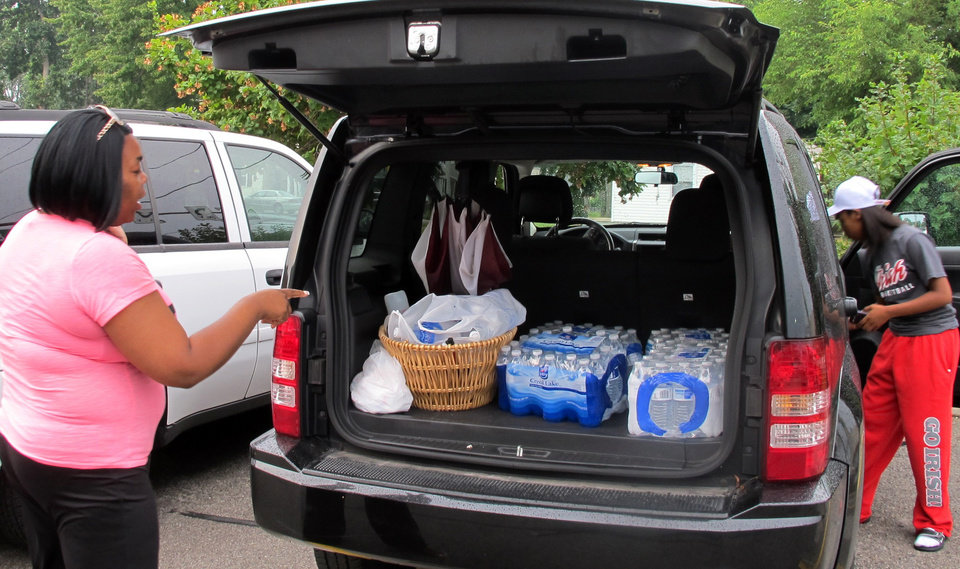 Photo - Aundrea Simmons stands next to her minivan with cases of bottled water she bought after Toledo warned residents not to use its water, Saturday, Aug. 2, 2014  in Toledo, Ohio. About 400,000 people in and around Ohio's fourth-largest city were warned not to drink or use its water after tests revealed the presence of a toxin possibly from algae on Lake Erie. (AP Photo John Seewer)