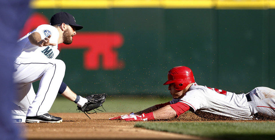 Photo -   Seattle Mariners second baseman Dustin Ackley, left, tags Los Angeles Angels' Mike Trout on a steal attempt at second base in the first inning of a baseball game Wednesday, Oct. 3, 2012, in Seattle. (AP Photo/Elaine Thompson)
