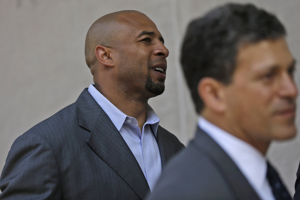 Photo - Former NFL player Dorsey Levens, left,  walks to the U.S. Courthouse Tuesday, April 9, 2013, in Philadelphia for a hearing to determine whether the NFL faces years of litigation over concussion-related brain injuries. Thousands of former players have accused league officials of concealing what they knew about the risk of playing after a concussion. The lawsuits allege the league glorified violence as the game became a $9 billion-a-year industry.  (AP Photo/Matt Rourke)