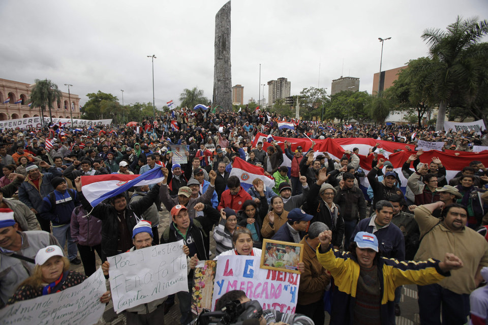 Photo -   Supporters of Paraguay's President Fernando Lugo protest against Lugo's impeachment trial, outside Parliament, in Plaza de Armas, Asuncion, Paraguay, Friday, June 22, 2012. Paraguayan lawmakers voted Thursday to impeach Lugo for his role in for his role in a deadly clash involving landless farmers and police. Lugo's trial was to begin Friday in Paraguay's Senate. (AP Photo/Jorge Saenz)