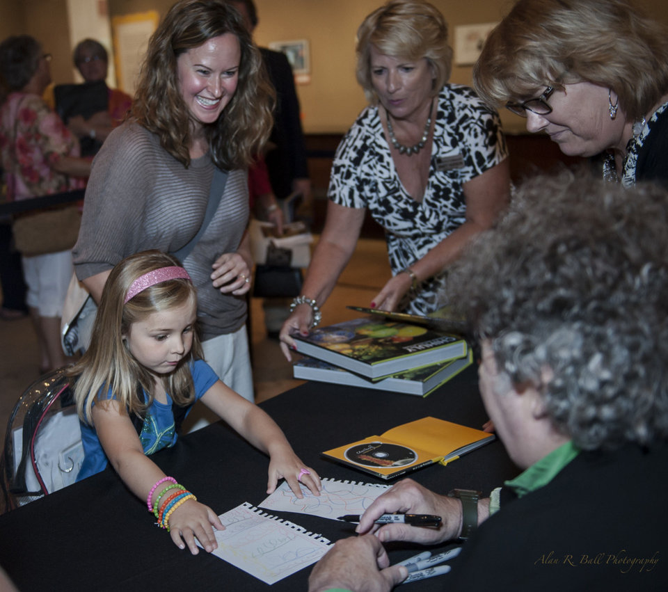 A young fan shows her artwork to famed glass artist Dale Chihuly during his June 24 visit at the Oklahoma City Museum of Art. Chihuly gave an invitation-only lecture at the museum, followed by a book signing for museum members. Photo provided by the Oklahoma City Museum of Art. <strong></strong>
