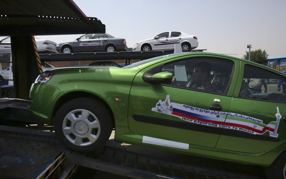 Photo - An Iranian car worker drives a sedan called Runna, manufactured by the state-run Iran-Khodro automobile company, up on a vehicle carrier truck in a ceremony marking the first shipment of automobiles to Russia since 2009, at company's plant near Tehran, Iran, Sunday, June 29, 2014. Iran began exporting automobiles to Russia for the first time in five years on Sunday, after meeting upgraded emission standards, the country's largest auto manufacturer said. (AP Photo/Vahid Salemi)