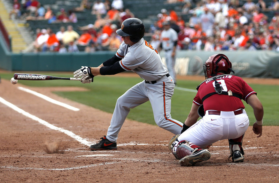 Oklahoma State\'s Donnie Walton hits the ball in front of Oklahoma\'s Anthony Hermelyn during the Bedlam baseball game between the University of Oklahoma and Oklahoma State University at the Chickasaw Bricktown Ballpark in Oklahoma CIty, Saturday, May 11, 2013. Photo by Sarah Phipps, The Oklahoman
