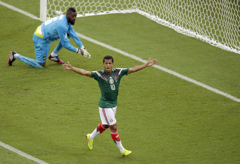 Photo - Mexico's Giovani dos Santos, right, reacts after a goal was disallowed while Cameroon's goalkeeper Charles Itandje looks on during the group A World Cup soccer match between Mexico and Cameroon in the Arena das Dunas in Natal, Brazil, Friday, June 13, 2014.  AP Photo/Hassan Ammar)