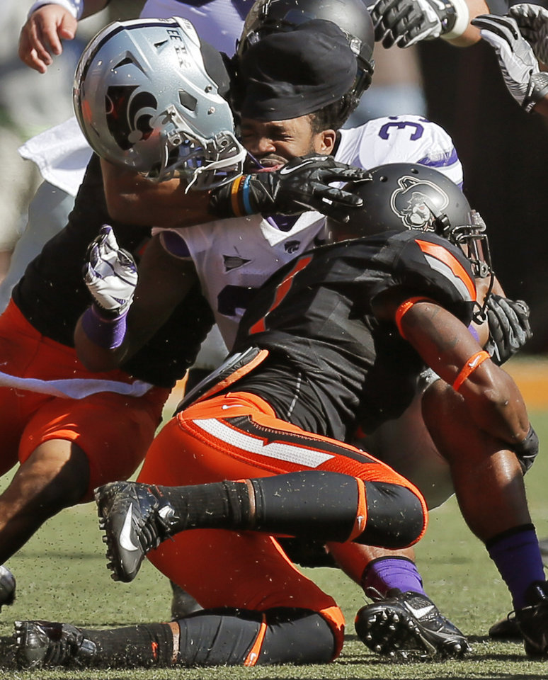 Kansas State\'s John Hubert (33) loses his helmet as he is stopped by a pair of OSU defenders during a college football game between the Oklahoma State University Cowboys (OSU) and the Kansas State University Wildcats (KSU) at Boone Pickens Stadium in Stillwater, Okla., Saturday, Oct. 5, 2013. Photo by Nate Billings, The Oklahoman
