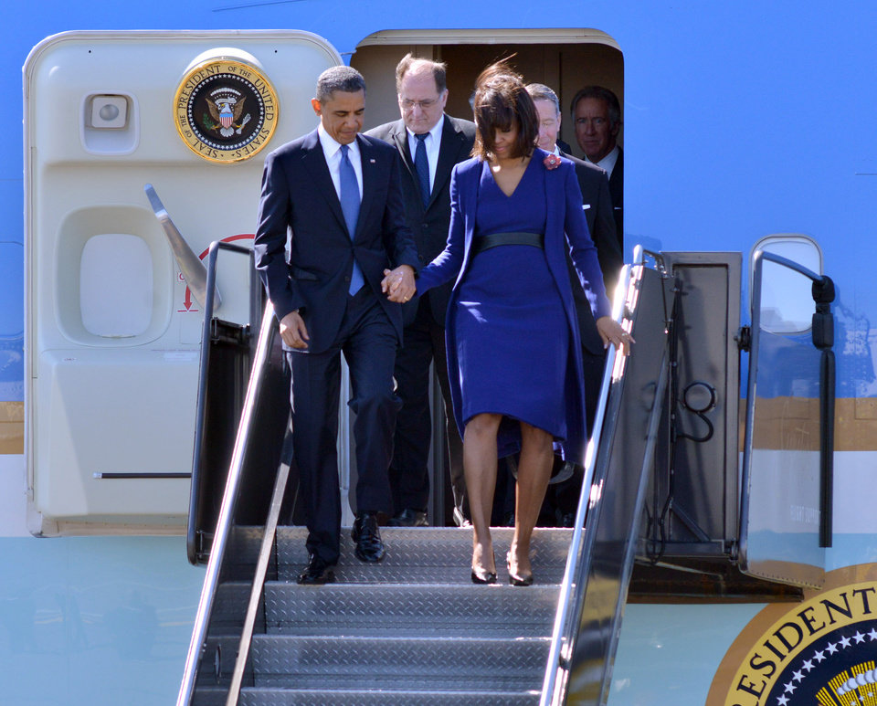 Photo - President Barack Obama  and first lady Michelle Obama depart Air Force One at Boston's Logan International Airport in Boston, Thursday, April 18, 2013, before attending an interfaith service for the victims of the bombings at the finish line of the Boston Marathon. Also seen is  Rep. Michael Capuano, D-Mass. is at center. (AP Photo/Josh Reynolds)