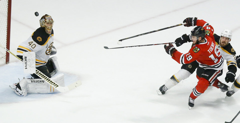 Photo - Chicago Blackhawks center Jonathan Toews (19) shoots the puck wide against Boston Bruins goalie Tuukka Rask (40) as Boston Bruins defenseman Andrew Ference (21) defends in the third period during Game 2 of the NHL hockey Stanley Cup Finals, Saturday, June 15, 2013, in Chicago. (AP Photo/Charles Rex Arbogast)