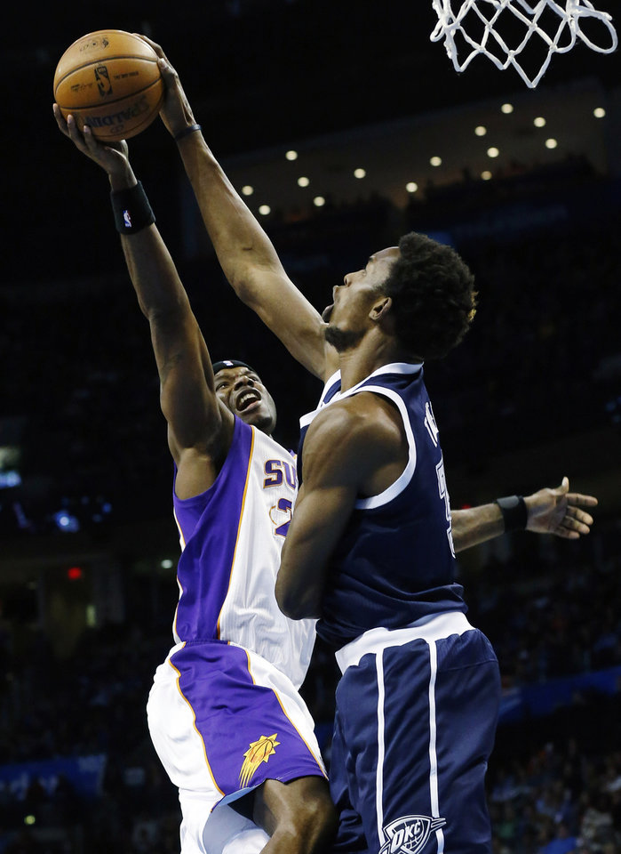 Photo - Oklahoma City Thunder center Hasheem Thabeet (34) blocks a shot by Phoenix Suns center Jermaine O'Neal (20) in the second quarter of an NBA basketball game in Oklahoma City, Monday, Dec. 31, 2012. (AP Photo/Sue Ogrocki)
