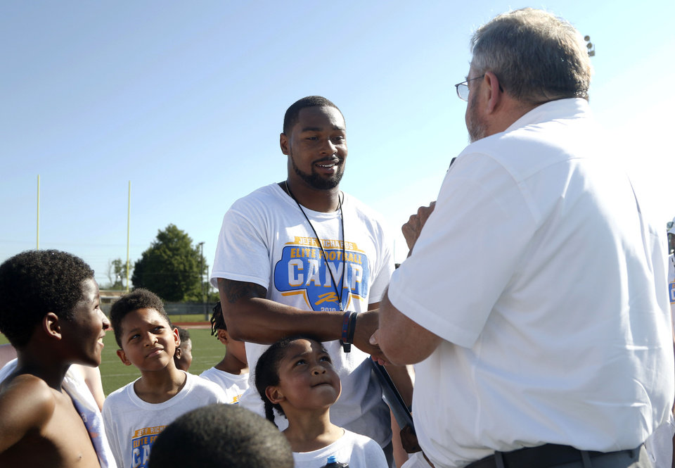 Photo - Los Angeles Chargers player Jeff Richards shakes hands with Del City Mayor Floyd A. Eason at the Jeff Richards Elite Football Camp at Del City High School in Del City, Oklahoma on July 13, 2019. [Paxson Haws/The Oklahoman]