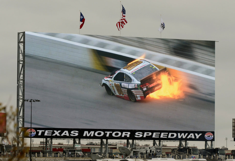 Photo - A video screen shows a replay of Dale Earnhardt Jr.'s (88) car during a wreck at the NASCAR Sprint Cup series auto race at Texas Motor Speedway, Monday, April 7, 2014, in Fort Worth, Texas. (AP Photo/Larry Papke)