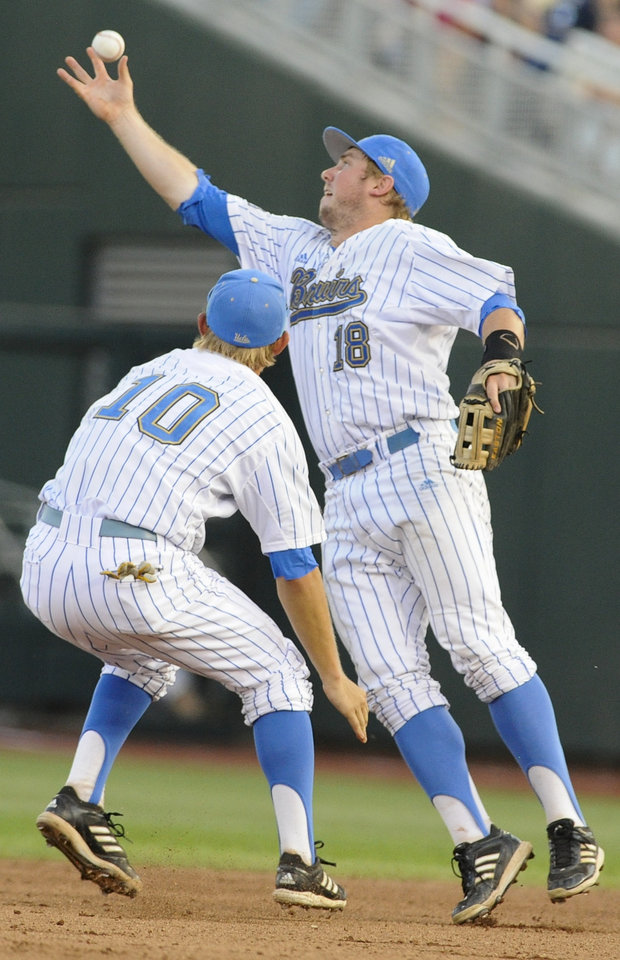 UCLA second baseman Cody Regis (18) uses a bare hand to catch a ball bobbled by shortstop Pat Valaika (10) which was hit for a single by North Carolina's Cody Stubbs in the fourth inning of an NCAA College World Series baseball game in Omaha, Neb., Friday, June 21, 2013. (AP Photo/Eric Francis)
