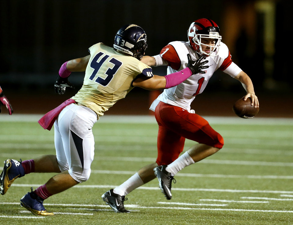 Photo - Lawton's Dallas Sealey (1) tries to get past Reece Gilbert as the Southmoore Sabercats play the Lawton High School Wolverines in high school football on Friday, Oct. 11, 2013, in Moore, Okla. Photo by Steve Sisney, The Oklahoman