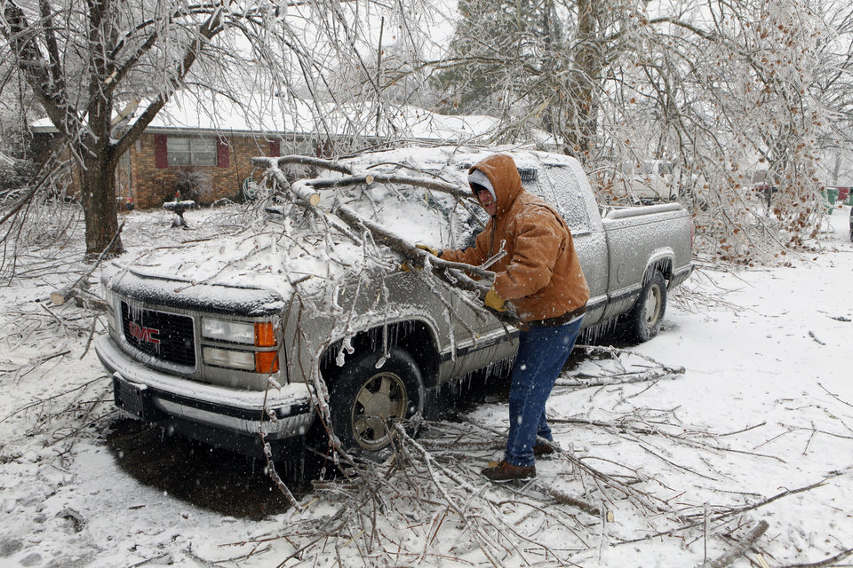 Photo - Jamie Cherry with Martin's Tree Service out of Crumville, Louisiana, removes tree limbs on Friday, Jan. 29, 2010, in Purcell, Okla. Power lines, homes and vehicles were damaged after a winter storm.  Photo by Steve Sisney, The Oklahoman