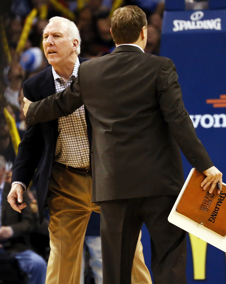Photo - San Antonio head coach Gregg Popovich is held back by an assistant as he yells at an official during a timeout in an NBA basketball game between the Oklahoma City Thunder and the San Antonio Spurs in Oklahoma City Monday, Dec. 17, 2012. Popovich was given a technical foul. Oklahoma City won, 107-93. Photo by Nate Billings, The Oklahoman