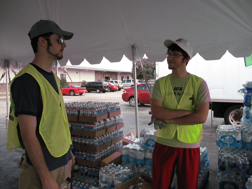 Photo - Austin Rupp and his brother Parker Rupp, both of Edmond, help distribute water at a disaster relief center set up at St. John's Lutheran Church, 1032 NW 12th in Moore. The brothers are volunteers from St. Mark Lutheran Church in Edmond. Photo by Carla Hinton  Carla Hinton - The Oklahoman