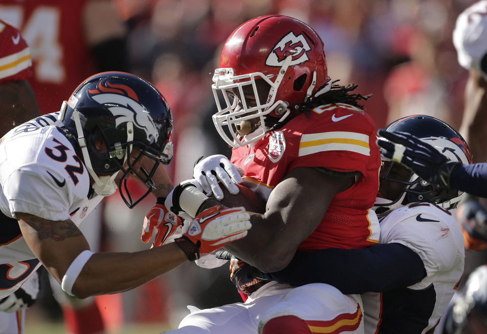 Photo -   Kansas City Chiefs running back Jamaal Charles (25) is tackled by Denver Broncos strong safety Mike Adams, right, and defensive back Tony Carter (32) during the first half of an NFL football game at Arrowhead Stadium in Kansas City, Mo., Sunday, Nov. 25, 2012. (AP Photo/Charlie Riedel)