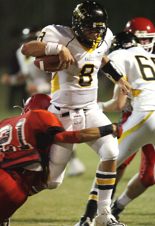 Photo - Madill's Spencer Bond (8) carries and Purcell's James Wolfe (21) tries to stop him in high school football as Madill plays at Purcell on Thursday, Oct. 1, 2010, in Purcell, Okla.  Photo by Steve Sisney, The Oklahoman