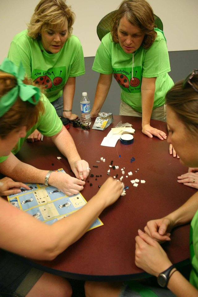 Are you sure this fits? Members of the Communication Disorders Lady Bugs try to complete one of the many tasks in the J. D. McCarty Center�s Amazing Race team building exercise held Tuesday, August 1. In this task a Leggo robot had to be assembled using only the directions provided in the package with no parts left over. At the table (l-r) are Caryl Hennen, Kelly Hawkins, Chrissy Hancock, Iris Reimann-Philipp and Julie Pryer. The Amazing race was the kickoff event for the McCarty Center�s employee appreciation month. The Lady Bugs finished the race tied for third place.<br/><b>Community Photo By:</b> Greg Gaston<br/><b>Submitted By:</b> Greg,