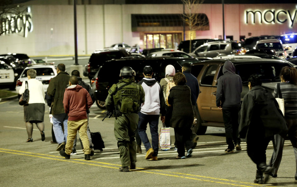 Photo - An official, center, wearing tactical gear leads a group of people out of the Garden State Plaza Mall during a lockdown following reports of a shooter, Tuesday, Nov. 5, 2013, in Paramus, N.J. (AP Photo/Julio Cortez)